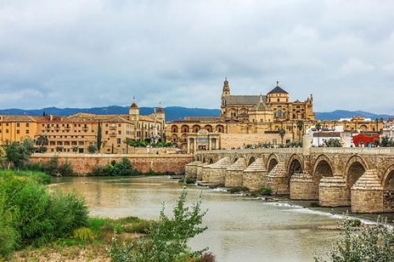 Roman Bridge on Guadalquivir river and Mezquita Cathedral (Great Mosque) at dawn in the city of Cordoba, Andalusia, Spain.